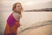 Beautiful woman walking on the beach and having fun