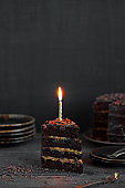 Piece of birthday chocolate cake with candle
