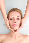 Young woman in spa gets a facial massage