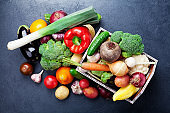 Wooden box with autumn harvest farm vegetables and root crops on black kitchen table top view.