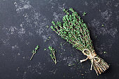Herb thyme on black kitchen table from above. Flat lay.