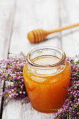 Honey in pot or jar and flowers heather on wooden rustic table.