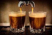 Espresso shots pouring into shot glasses.