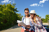 Cheerful young couple on a sunny day reading map