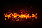 Line of blazing fire isolated on black with bright sparks