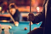 Close up of unrecognizable man with a pool cue in pool hall.