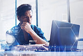 Concept of digital screen,virtual connection icon,diagram,graph interfaces.Young banking finance analyst working at office on laptop.Businessman analyze stock reports.Blurred background,horizontal.
