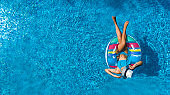 Aerial top view of beautiful girl in swimming pool from above, relax swim on inflatable ring donut and has fun in water on family vacation