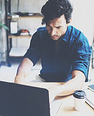 Young attractive man working at sunny office on laptop while sitting at wooden table.Businessman analyze digital reports on notebook computer.Blurred background.Vertical.