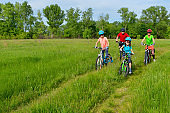 Family on bikes outdoors, happy active parents and two kids cycling outdoors on spring meadow, fitness and healthy lifestyle concept