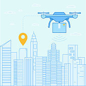 Drone quadcopter  flying over city landscape with box