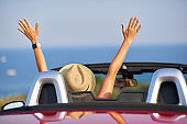 Beautiful woman having fan on vacation with convertible car