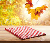 Empty wooden deck table with tablecloth over bokeh autumn leaves background. Kitchen background, product montage display. Mock up .