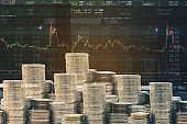 Double exposure of stock graph and rows of coins with flare light for finance and business trading concept.