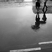 Reflection of people with umbrellas in puddles on the asphalt.
