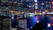 Hong Kong Victoria harbour and its iconic red ancient junk sail zoom shot from the Peak at night