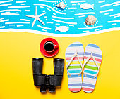 Summertime flip-flops and coffee cup with binocular
