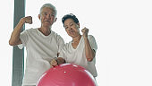 Happy old senior Asian couple have fun with gym yoga ball class