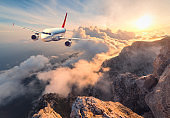 Airplane is flying over clouds at sunset. Landscape with white passenger airplane, mountains, sea and orange sky with sun in summer. Passenger aircraft is landing. Business travel. Commercial plane