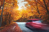 Blurred car going mountain road in autumn forest at sunset. Car in motion in the evening. Beautiful landscape with asphalt road, red car, colorful orange forest and yellow sunlight. Travel background