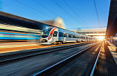 Speed train in motion at the railway station at sunset in Europe. Modern intercity train on the railway platform with motion blur effect. Industrial scene with moving passenger train on railroad