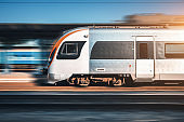 Speed train in motion at the railway station at sunset in Europe. Modern intercity train on railway platform with motion blur effect. Moving passenger train on railroad. Transportation. Vintage