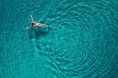 Aerial view of swimming woman in Blue Lagoon. Mediterranean sea in Oludeniz, Turkey. Summer seascape with girl, clear azure water, waves in sunny day. Transparent water. Top view from flying drone