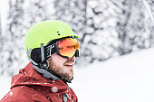 Happy Snowboarder Wearing Helmet and Goggles at The Ski Mountain