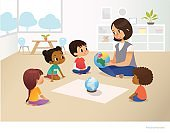 Smiling kindergarten teacher shows globe to children sitting in circle during geography lesson. Preschool activities and early childhood education concept. Vector illustration for poster, flyer.