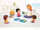 Children sit around world map and redhead female teacher demonstrates them model of planet Earth. Geography lesson at primary school concept. Vector illustration for poster, postcard, advertisement.