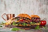 Tasty burgers on wooden table