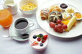 Rich continental breakfast. French crusty croissants, muesli, lots of sweet fruits and berries, hot coffee for morning meals.
