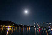 City by the sea in the night with full moon with yachts and boats