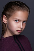 Closeup portrait of cute little girl with dark hair in studio over grey background.
