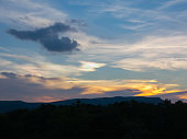 Dark mountain and forest on blue sky and cloud on sunset