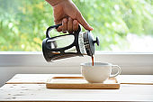 Hands holding french press coffee pot and white cup