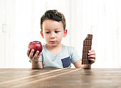 Child is choosing between chocolate and apple.