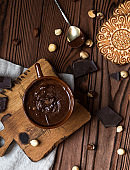 hot chocolate in brown cup on a wooden desk with nuts, cookies and pieces of chocolate on a brown wooden table
