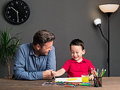Father and son painting a sun with watercolor