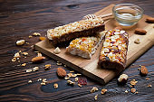 Various granola energy bars with nuts, dry fruits and chocolate, on the dark brown wooden table, gluten free