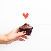 Valentine's Day concept. A woman holds a chocolate capcake in her hand with a paper heart on a stick.