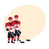Two hockey players in Canadian uniform standing and holding sticks