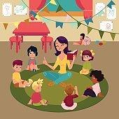 Kindergarten kids listen to teacher reading a book