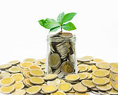 many coins currency Thai Baht lay down on white background around many coin over flow from glass bottle with plant growth on coin in bottle for saving. growth financial and saving concept.