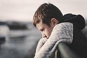 Sad little boy leaning over railing