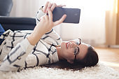 Woman lies on carpet reading on tablet or sending message, communication