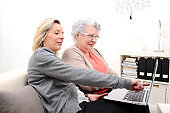 attractive 40 years old woman helping with computer her mother for internet search , 80 years old senior woman at home