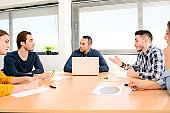 young casual and dynamic new business people team man and woman discussing on informal meeting with the company manager in office