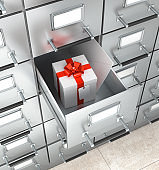 Archival storage locker. White box with a red bow, an envelope in a drawer