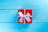 Christmas gift box against blue wooden background. Holiday greeting card. Flat lay